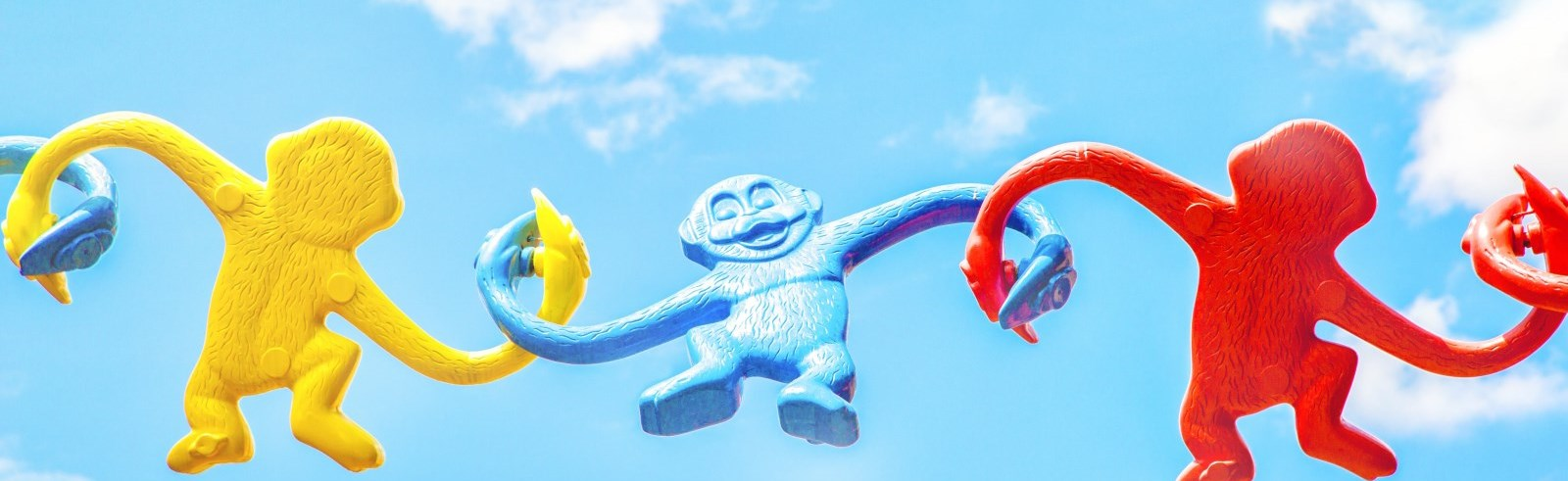 Colourful plastic monkeys linked by their arms with a blue sky background
